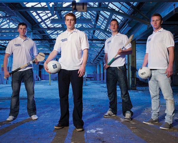 image shows 4 GAA athletes in white electric ireland t-shirts. They are all looking down towards the camera. Two are holding balls and two are holding hurls.
