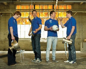 image shows 4 GAA athletes in blue t-shirts. Two are holding trophies and two are holding footballs