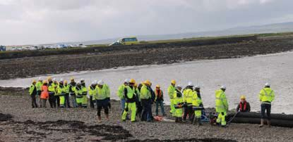 image shows a wide shot of an oil spill exercise. We can see a number of people in safety gear on a beach with a huge black pipe.
